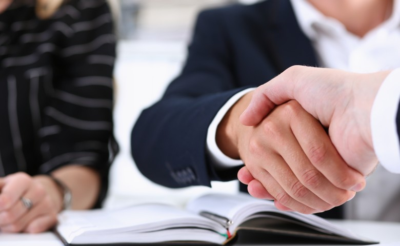 Man in suit shake hand as hello in office closeup